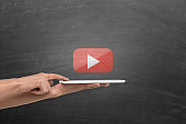 Woman holding digital tablet under you tube play icon on blackboard