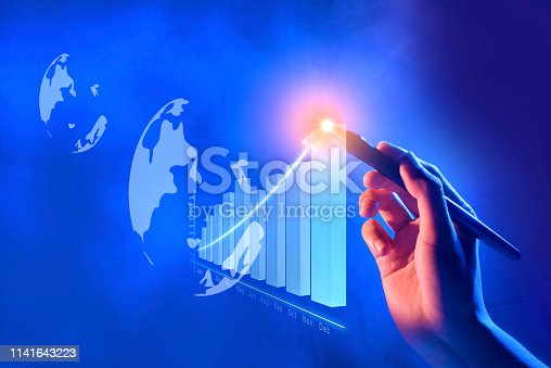 Business hand with marker draw a increases financial chart on virtual screen which display the interface of globe. Digital technology concept