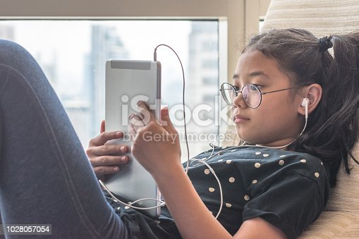 istock Digital technology lifestyle of school girl child or student using wireless internet for distance learning application and reading e-book app on mobile ipad smart device multimedia computer tablet 1028057054