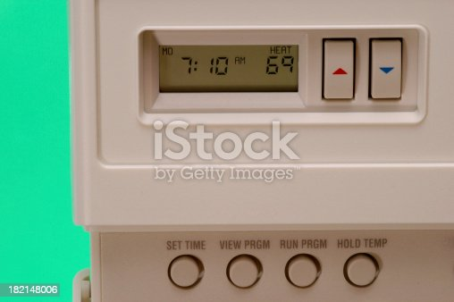 A macro image of a digital heating and cooling thermostat.