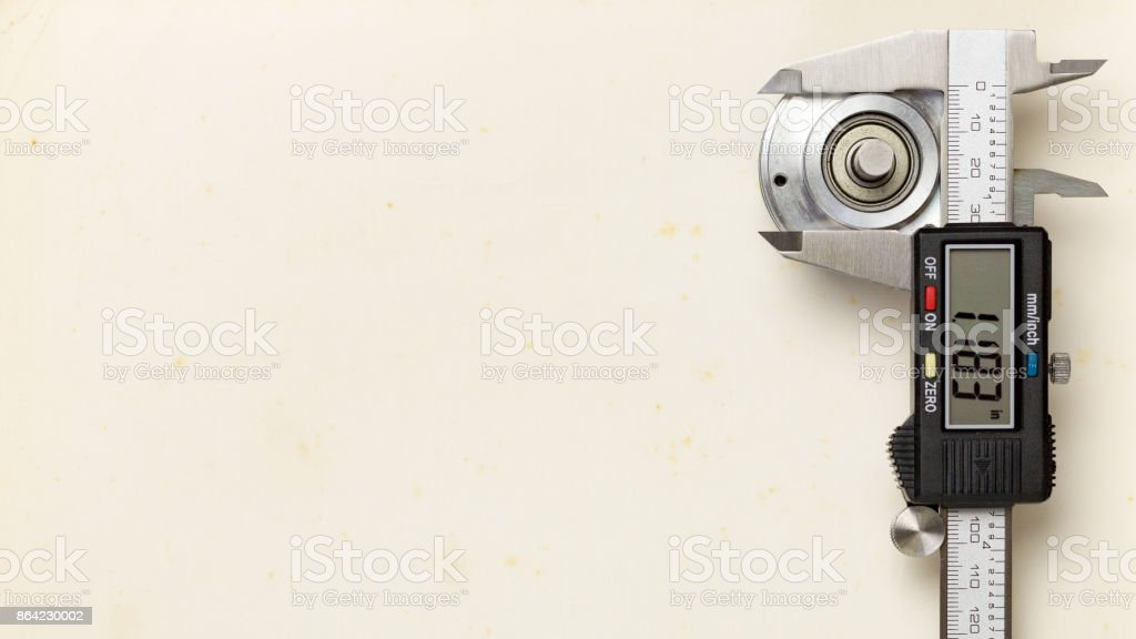 Digital vernier caliper measuring the outer diameter of the encoder unit placed on the old paper background, 7-segment display the accuracy of measurement value royalty-free stock photo