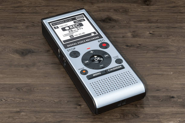 digital voice recorder, dictaphone on the wooden table. 3d rendering - dictaphone stock pictures, royalty-free photos & images