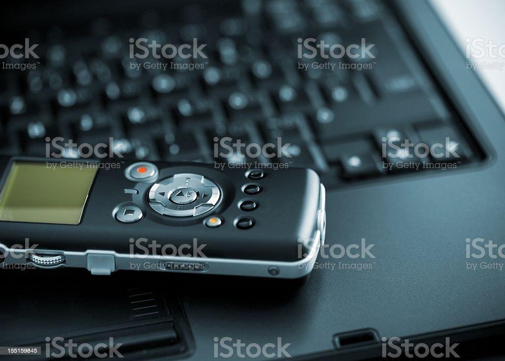 Digital Voice Recorder lying on laptop stock photo