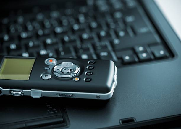 digital voice recorder lying on laptop - dictaphone stock pictures, royalty-free photos & images