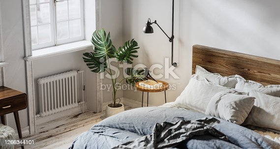 Digitally generated domestic bedroom interior. 3d render of bedroom with bed, heater, potted plant and side table.