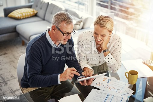 Shot of a mature couple using a digital tablet while going through paperwork at home