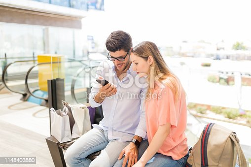 Young couple checking offers on smartphone while sitting in shopping mall
