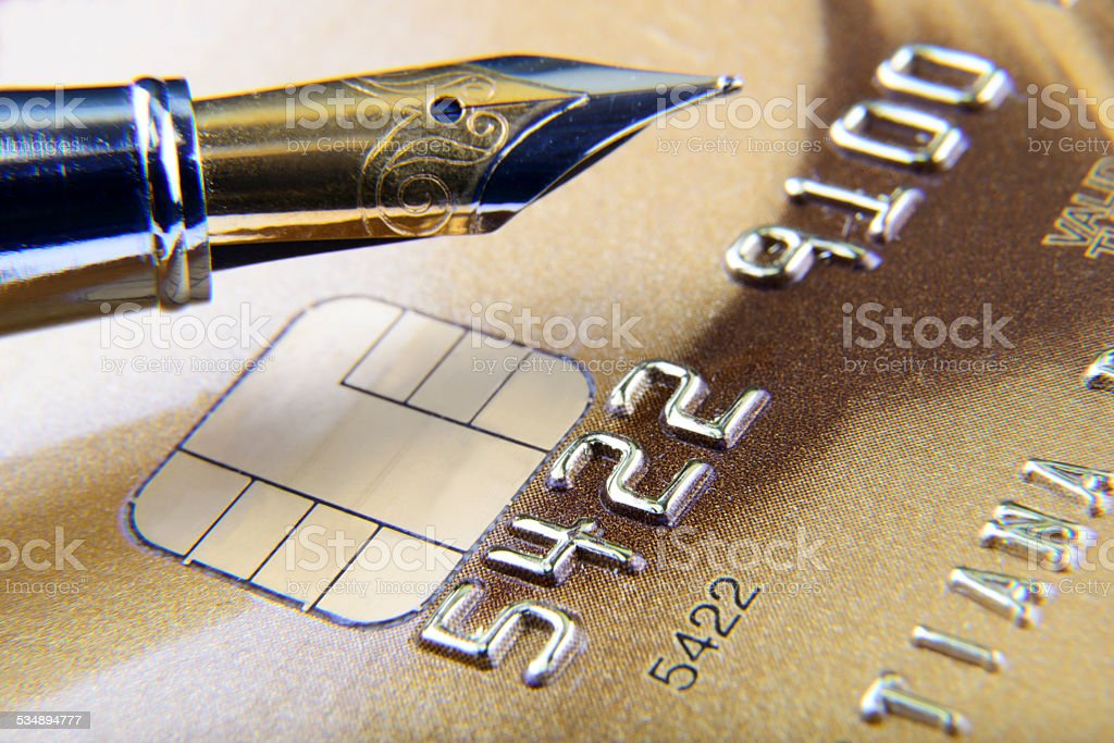 digits and pen on credit card close-up stock photo