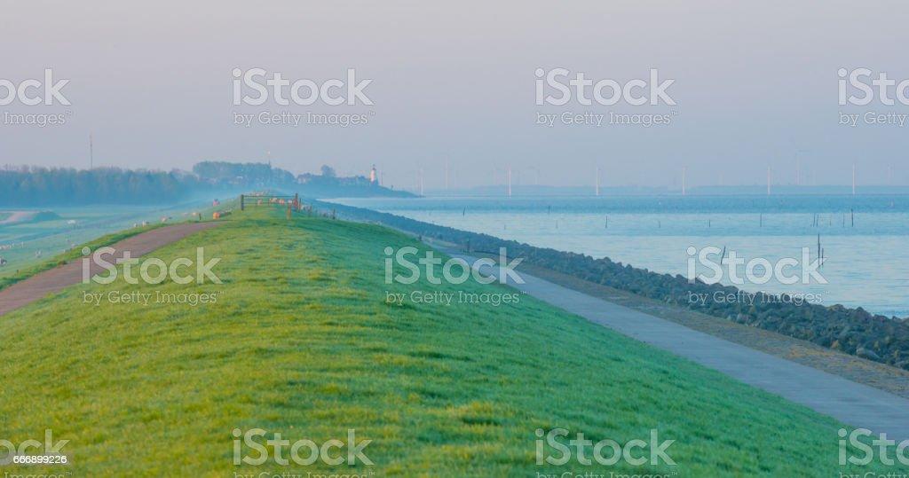 Dike along a lake at sunrise stock photo