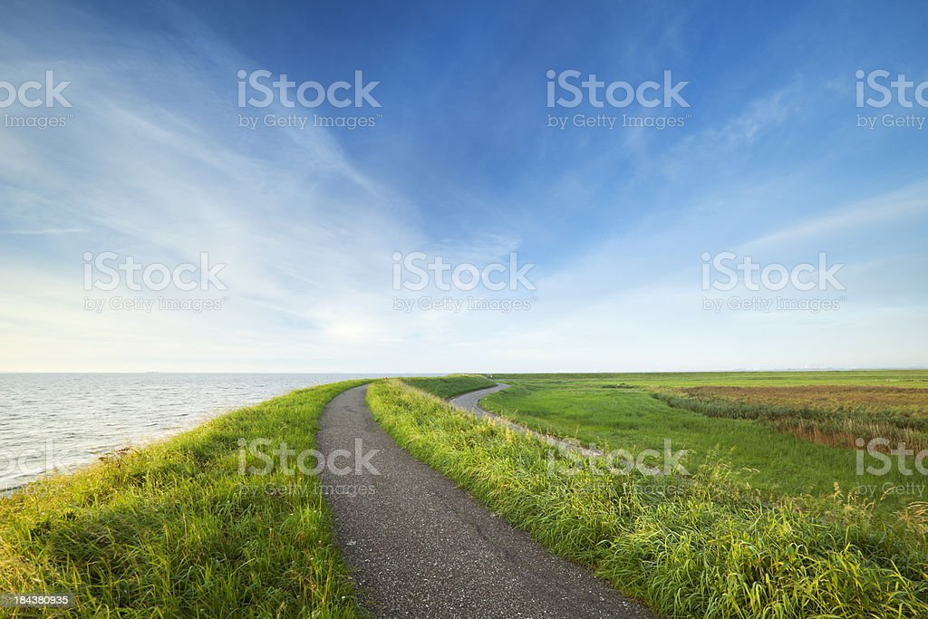 Dike in typical Dutch landscape in early morning sunlight stock photo