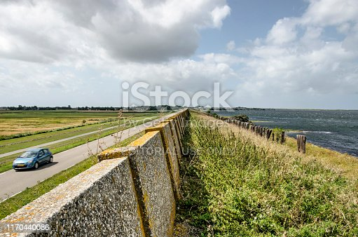 View along the dike on the north coast of the island of Schouwen-Duiveland, The Netherlands, with a weathered concrete wall, Lake Grevelingen on one side and a road and meadows on the other side