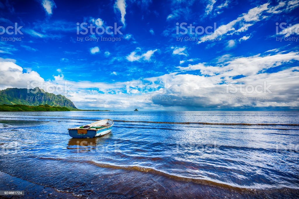 Dilapidated Fishing Boat on a Hawaiian Lagoon An old worn row boat on the shores of Kaneohe Bay on the north shore of Oahu, Hawaii. Abandoned Stock Photo