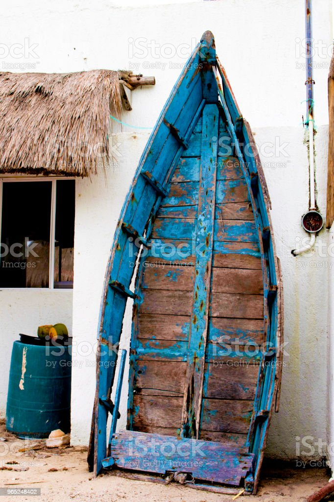 Dilapidated old boat leaning against stucco wall Yucatan Mexico zbiór zdjęć royalty-free