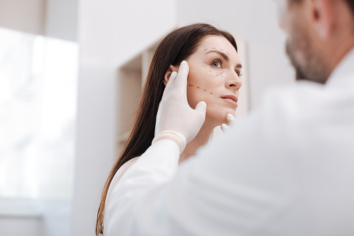 istock Diligent bright plastic surgeon in the middle of the process 696897538