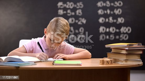 istock Diligent schoolboy doing his math homework, solving difficult tasks from book 1172311861