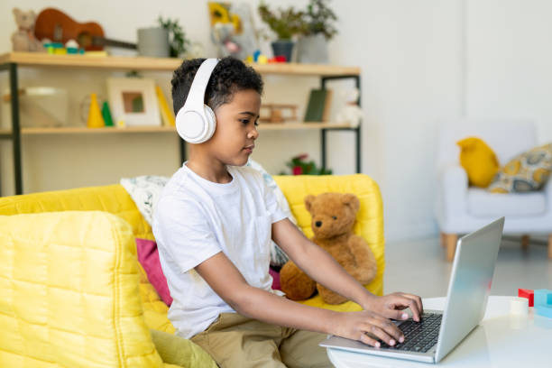 Diligent schoolboy of elementary age in headphones pushing laptop buttons stock photo