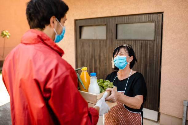 Diligent volunteer deliver a packet of food to a people in need during quarantine stock photo