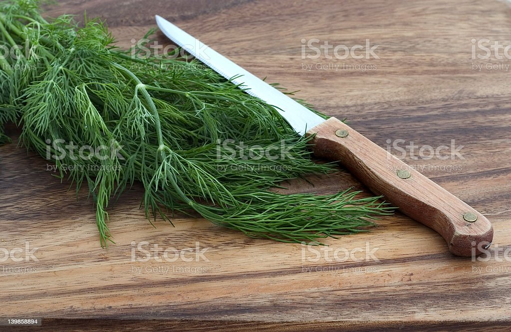 dill and knife on a cutting board stock photo