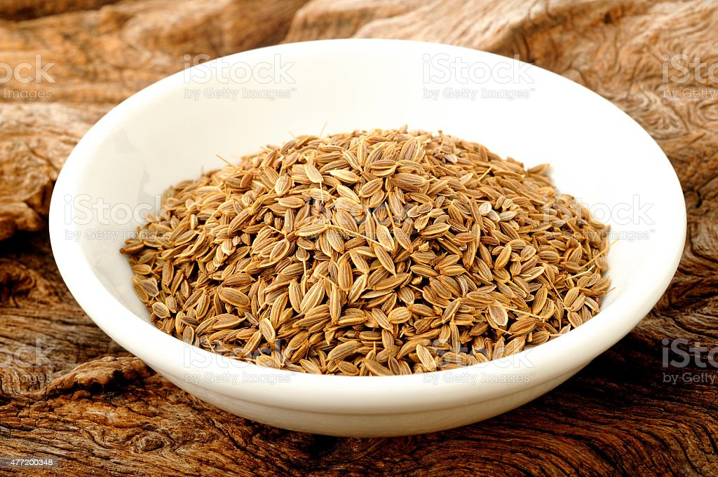 dill seeds in white bowl stock photo