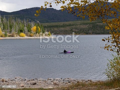 DILLON, COLORADO—OCTOBER 2017: Framed scenic view of Dillon Lake or Dillon Reservoir with a woman paddling a purple kayak one beautiful day in autumn.