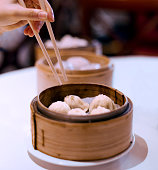 Dim sum in a bamboo basket with a hand holding chopsticks going to pick a piece up.
