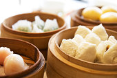 Close-up on a variety of dim sum in bamboo steam containers.