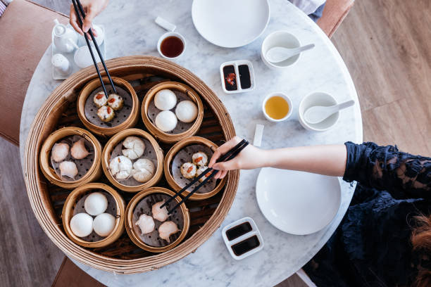 dim sum set: barbecued pork bun, shrimp dumpling, sweet cream buns, shrimp shumai topping with goji berry served in steamer baskets with hands using chopsticks. - dumplings stock photos and pictures