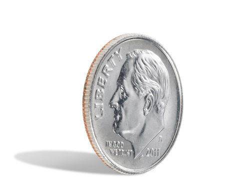 A US dime, ten cents, isolated on a white background with a shadow. There is a clipping path which may be used to delete the shadow if desired.
