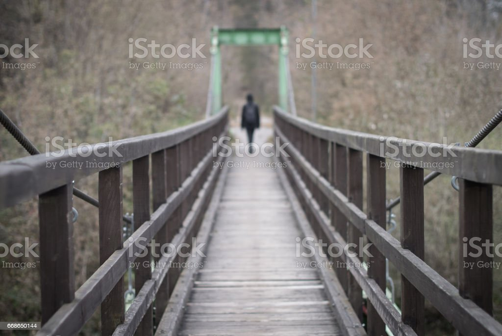 Diminishing perspective with a suspension bridge and a woman disapearing in the distance. stock photo