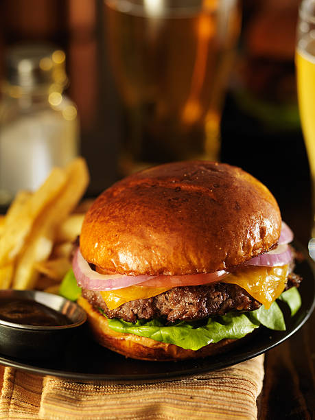 dimly lit cheeseburger in warm light - dimly stock pictures, royalty-free photos & images