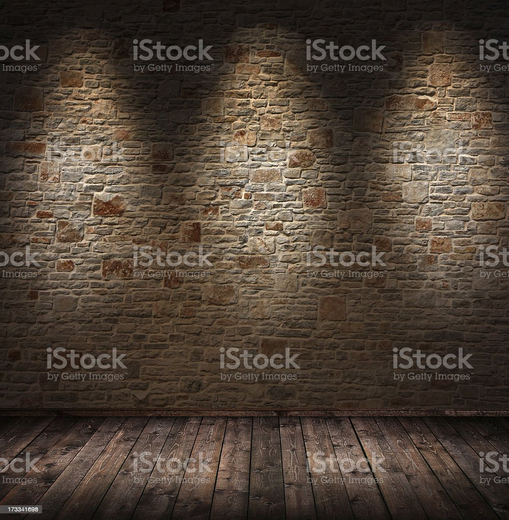 Dimly lit interior room with stone wall and wood floorboards stock photo
