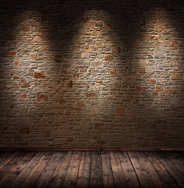 dimly lit interior room with stone wall and wood floorboards - dimly stock pictures, royalty-free photos & images
