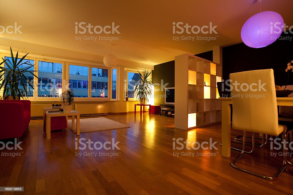 Dimly lit living room with wood floors stock photo
