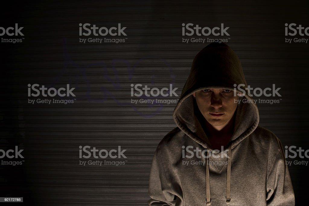 Dimly lit menacing man in gray hooded sweatshirt stock photo