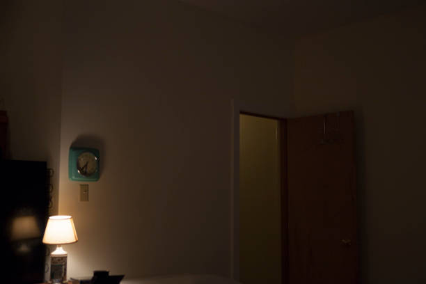 dimly lit room with a wall clock - low lighting stock photos and pictures