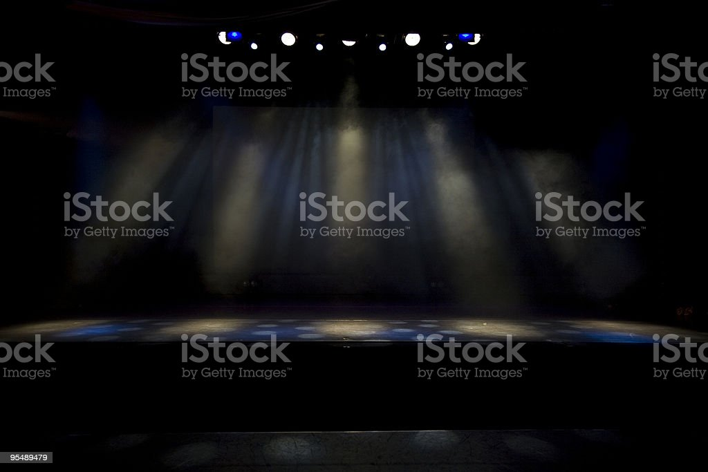 A dimly lit stage with several spotlights shining royalty-free stock photo