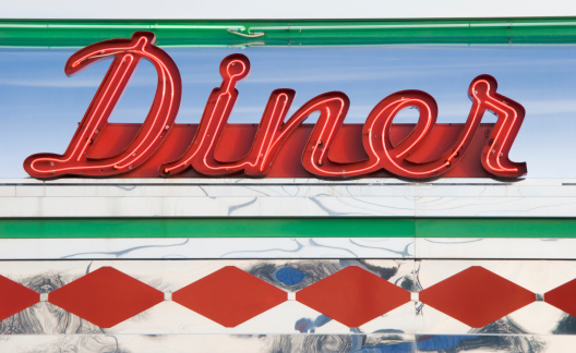 Diner sign in red neon at a roadside restaurant, close up, retro americana in vintage style, USA.