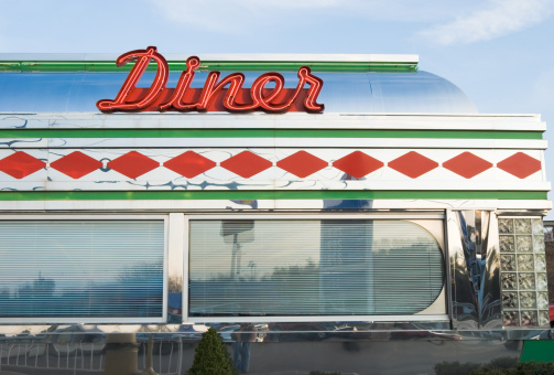 Diner with sign in bright red neon and chrome, 1950's retro style restaurant, vintage roadside Americana, USA.