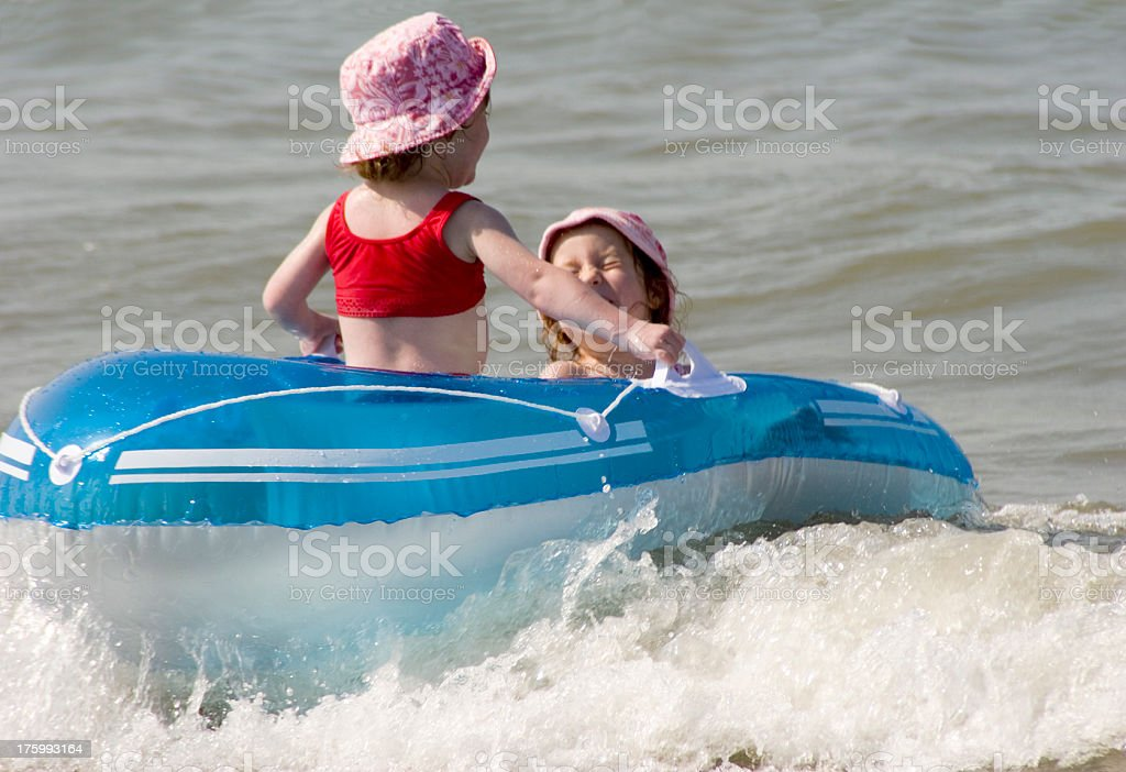 """Dinghy fun for sisters """"Two little girls all alone in a blue dinghy, having lots of fun."""" Adventure Stock Photo"""