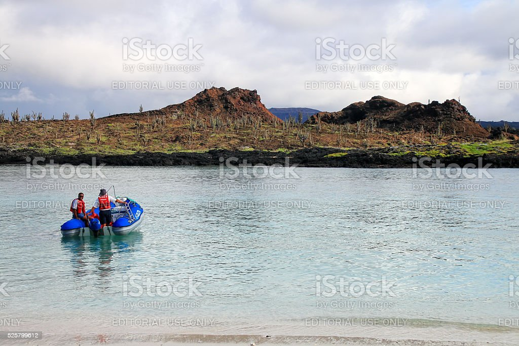 Dinghy motoring from the beach of Chinese Hat island, Galapagos stock photo