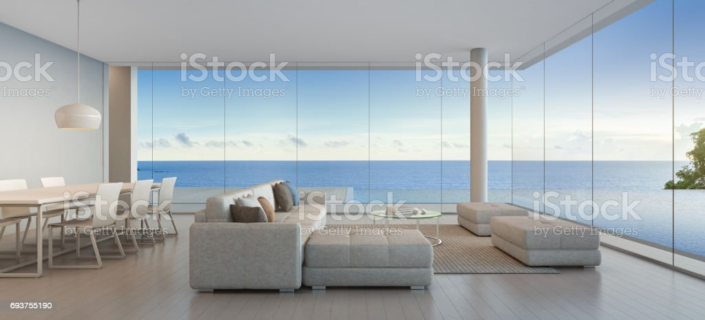 Dining and living room of luxury beach house with sea view swimming pool in modern design, Vacation home for big family stock photo