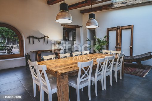 Wide angle view of dining area with large wooden table and chairs in traditional Spanish farmhouse featuring arched window, beamed ceiling, and slate flooring.