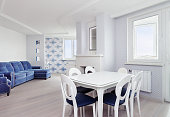 Dining area in white modern apartment with dining table and chairs for six with window and blue furniture background. Light home relaxation interior concept.