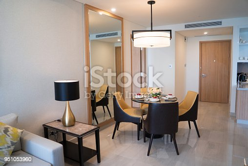Dining area of comfortable studio flat or hotel room. Set dining table prepared for dinner with Asian cuisine. City apartment and interior concept