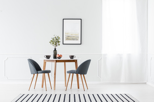 Small dining furniture set and a striped rug in a minimalist white interior with art above the table