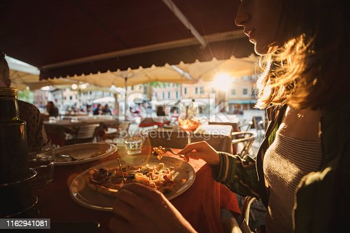 A side view shot of a lady eating pizza at an outdoor restaurant under the sunlight.