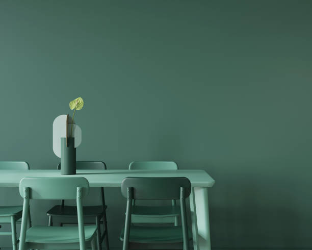 Dining room in monochrome green with a large table, chairs and a vase. stock photo