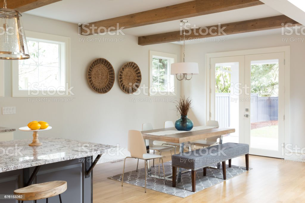 Dining room in new luxury home with French doors leading to backyard stock photo