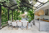 Open kitchen with empty dining room table and chairs outside, against green fresh plants on background