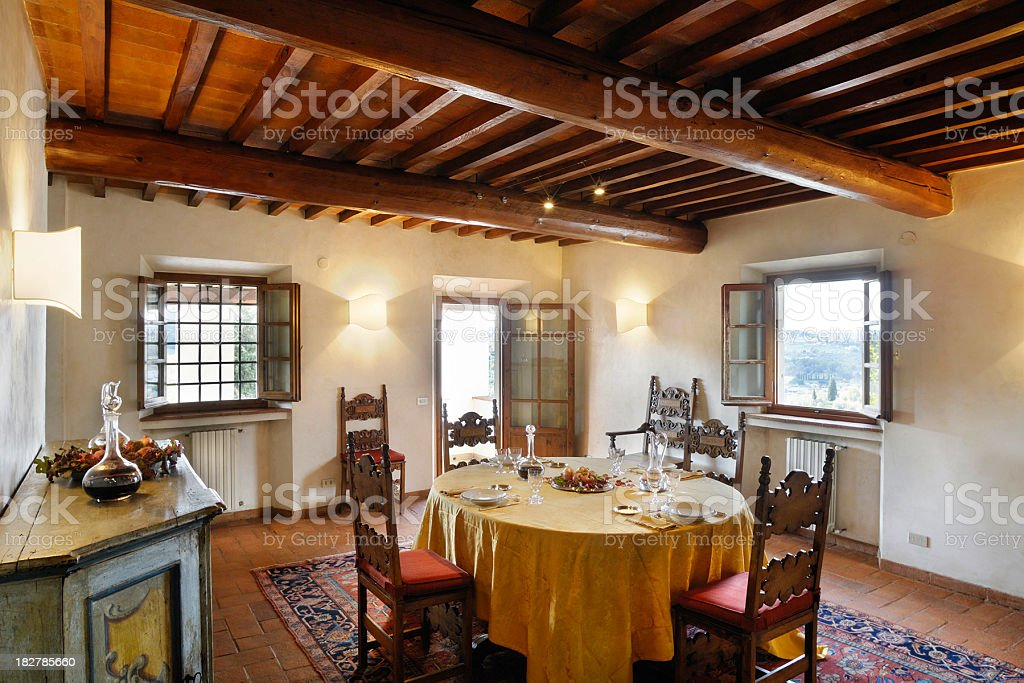 Dining room, table set, wooden ceiling beams, floor in terracotta stock photo